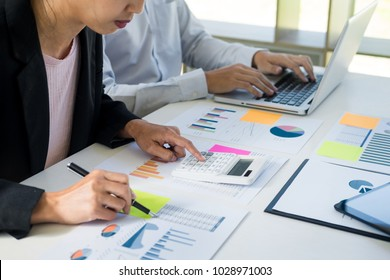Business man working at office with laptop, tablet and graph data documents on his desk. and secretary making report, calculating balance, Audit team work discussting concept