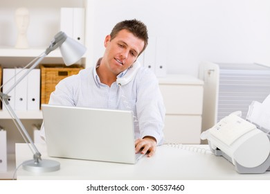 Business man working on computer at home calling on phone.