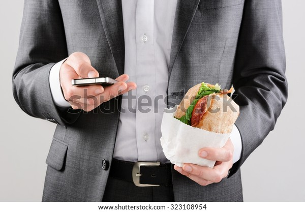 Business man working on the go with smart phone and take away sandwich lunch