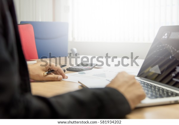 Business man working on his wooden table in the office with calculator,document,smart phone,pen and laptop in business,finance and banking concept