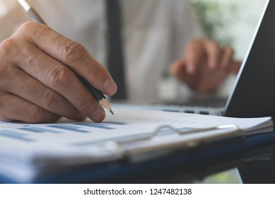 Business man working on laptop computer, reviewing business marketing report, financial data, spreadsheet on office desk with copy space, close up. Business strategy analysis concept