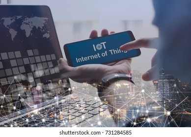 Business man working on laptop computer, holding mobile smart phone, internet of things IoT on blue screen, wireless network connecting double exposure with cityscape, Internet of Things IoT concept