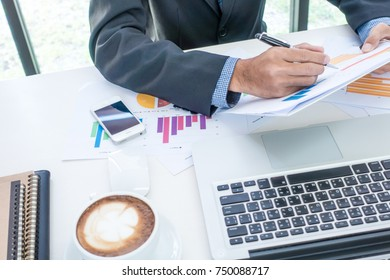 Business man working on business office desk with laptop, report papers and coffee. Office table.