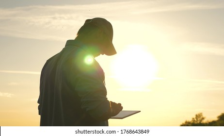 business man working with tablet outdoors. Farmer works with a tablet on a wheat field in the sun. silhouette of an agronomist with tablet studying a wheat crop in a field.