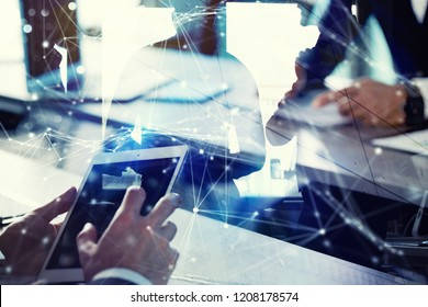 Business man works in office with tablet in the foreground. Concept of teamwork and partnership. double exposure with network effects