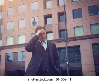 A business man is worried and stressed in a suit outside a city for a financial, unemployment or economy concept.