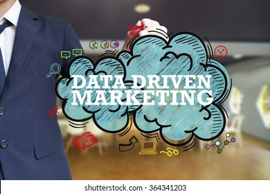 business man writing DATA DRIVEN MARKETING over the cloud with office background , business concept , business idea