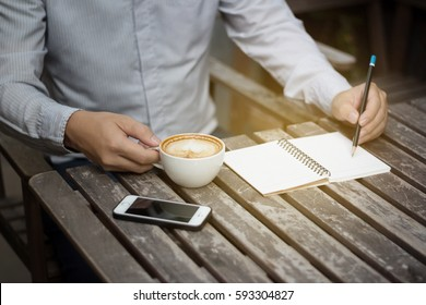 business man writing note and drink coffee on table