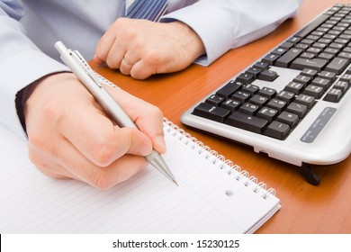 Business man writing in a notebook