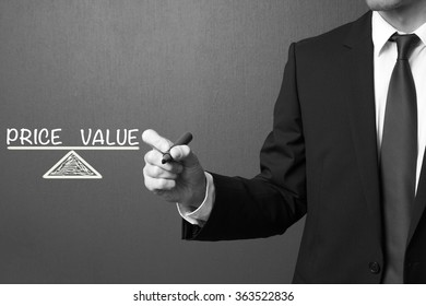 Business man writing Price and Value - Business Concept