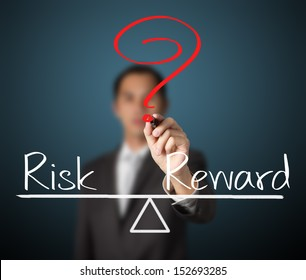 business man writing question with risk compare to reward on balance bar