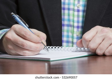 A business man is writing a something on a notepad. The man is wearing business outfit.