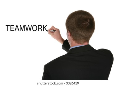 A business man writing the word teamwork on the board
