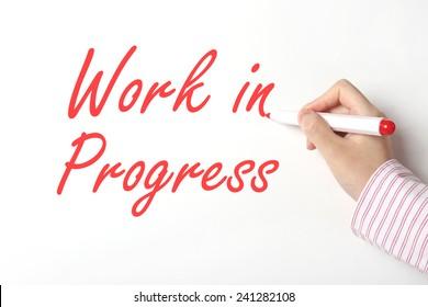Business man writing work in progress word on whiteboard