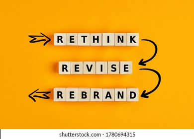 Business management branding concept of rethink revise and rebrand words on wooden cubes with process arrows.