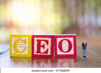 Business and Management Concept. Businessman miniature figure standing next to C E O alphabet wooden blocks toy.