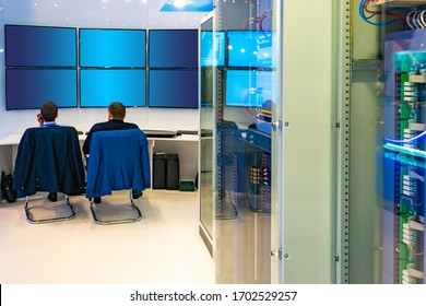 Business management. People in the control center. Monitoring the situation. Monitors in the control center. Empty screens of monitors. Cabinets with network equipment. Enterprise management point.