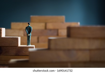 Business, management, strategy concept. businessman figure  hands clasped behind back stand on wooden block ladder