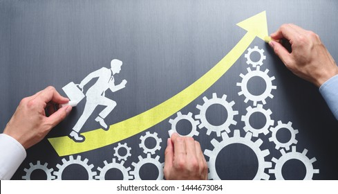 Business management and teamwork concept.  Three people drawing gears, arrow and running businessman on chalkboard.