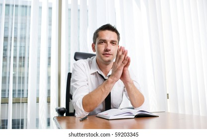 Business manager clasped his hands in front of him while sitting at the table in board room. Handsome man in business suit posing for the camera.