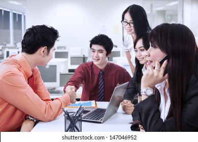 Business manager congratulate his partner while one woman calling at the office