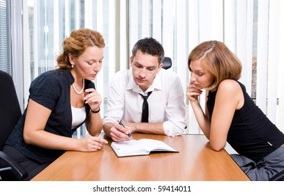Business manager drawing diagrams for his colleagues in notebook while they are sitting at the table and listening to him very attentively in board room Hi Res.