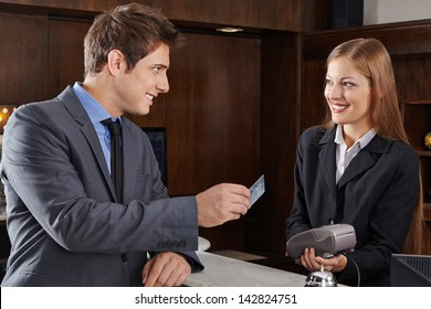 Business manager at hotel reception paying with credit card