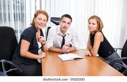 Business manager spaeaking with his office workers in board room while sitting at the table and looking at the camera.