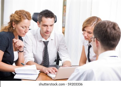 Business manager typing something on laptop computer while his office workers sitting round table looking at the screen and communicating with their boss in board room Hi Res.