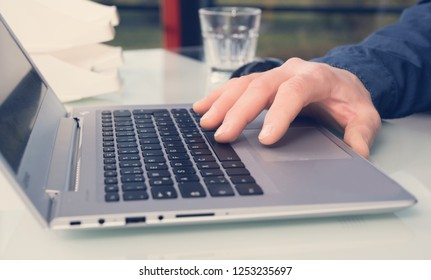 business mans hand on computer keyboard in office