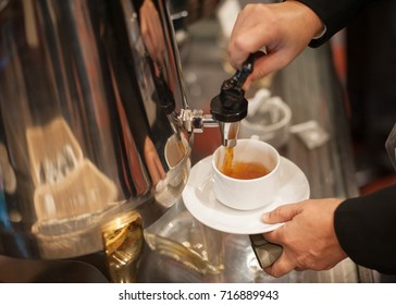 A business man's hand pouring tea into a white tea cup at the hotel during the hi-tea event.
