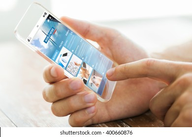 business, mass media, information, technology and people concept - close up of male hand holding and showing transparent smartphone with world news web page