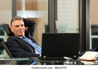 Business - mature boss contemplating in his office
