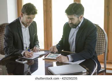 Business meeting. Bearded young man pointing at the screen of a tablet with information displayed in graph form while his coworker is taking notes in a notebook. All screen graphics are made up.