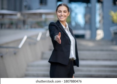 Business meeting. Beautiful woman in a suit stretching her hand in greeting