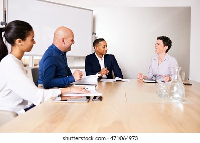 Business meeting between four eclectic partners as the mature white female laughs along with the other partners to a joke told by her colleague to break the ice.
