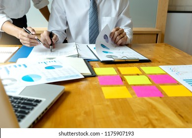 Business meeting businessman and businesswoman work on the table have graph chart and color notepad  paper