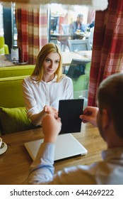Business meeting in a cafe. man shows a tablet to surprised woman