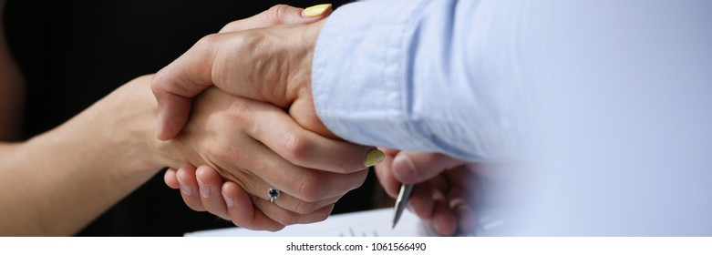 Business meeting in a cafe young businessmen make deal handshake