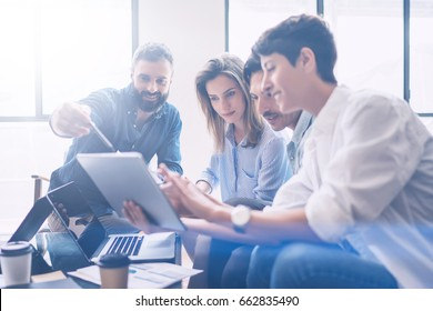 Business meeting concept.Coworkers team working new startup project at modern office.Analyze business documents, using touch tablet.Blurred background.Horizontal.