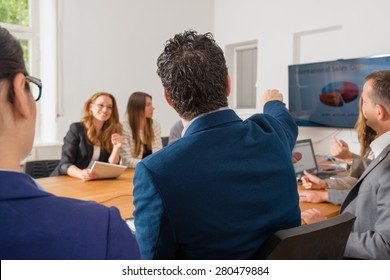 Business meeting in a conference room discussing international sales chart - mixed caucasian team rather casual, ambiente might suggest a startup or an agency