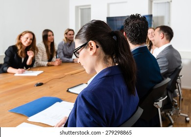 Business meeting in a conference room - mixed caucasian team rather casual, ambiente might suggest a startup or an agency