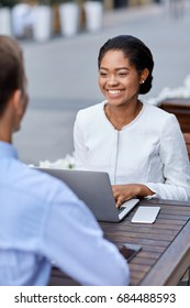 Business meeting - elegant african american girl working with laptop and smart phone smiling and talking to unknown blurred man sitting at table of street cafe