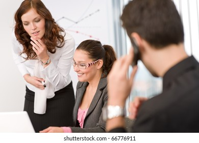 Business meeting - group of people in office sitting at laptop
