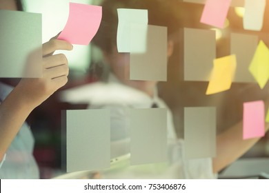 Business meeting Hands using sticky note on windows wall with post it on memory.