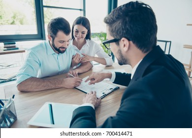 Business meeting. Happy couple is buying new house, young bearded attractive brunet lawyer in a formal wear is presenting contract to sign, they are in his office