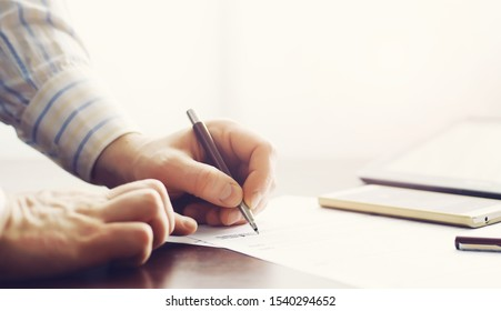 Business meeting. A man signs a contract. Male hand with pen makes notes in office.