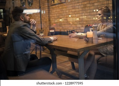 Business meeting of man and woman. Couple in love at the restaurant. Valentines day with sexy woman and bearded man. Date of family couple in romantic relations, love. Proposal and anniversary