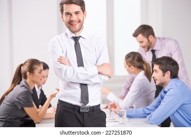 Business meeting - manager discussing work with his colleagues. man standing on foreground with crossed hands and team on background