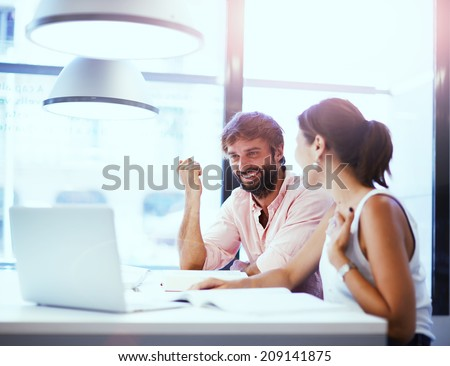 Business meeting in office, businesspeople working with laptop, couple of beautiful colleagues smiling having a work, two partners having good idea smiling together, teamwork with businesspeople